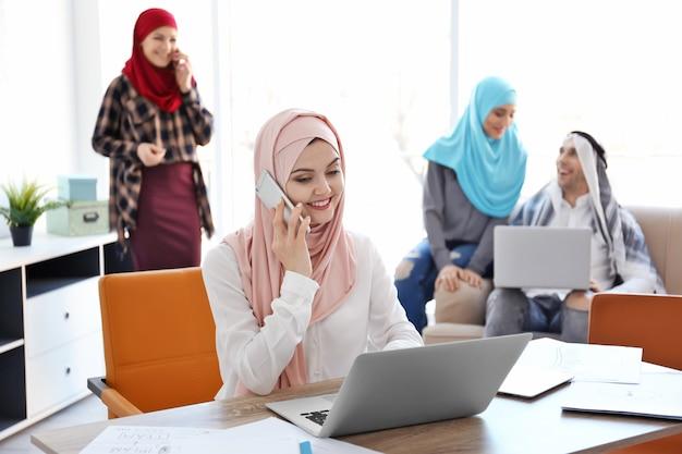 Мусульманская бизнес-леди в традиционной одежде разговаривает по телефону на рабочем месте