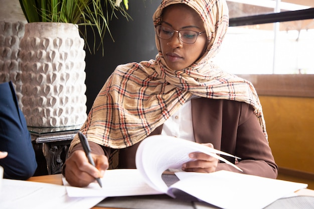Muslim businesswoman scanning contract