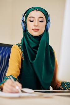 Muslim businesswoman taking notes