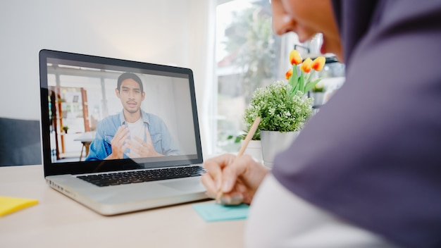 Muslim businesswoman using laptop talk to colleague about plan by video call brainstorm online meeting while remotely work from home at living room.