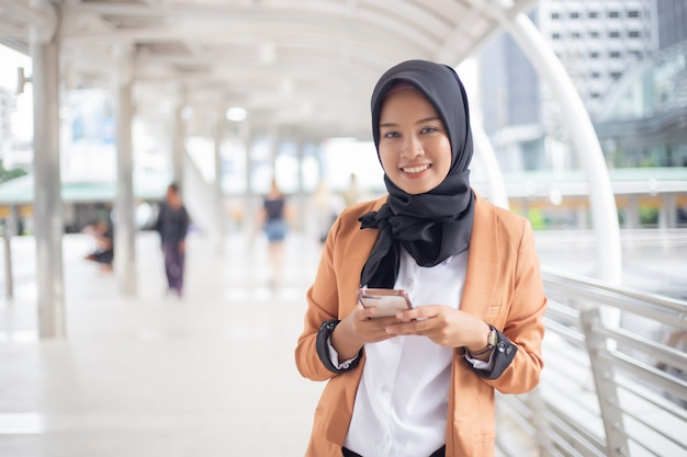 Muslim businesswomen in hijab using smartphone in city.