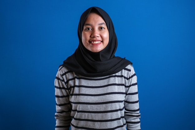 Muslim college student girl smiles to camera against blue background with confident gesture.