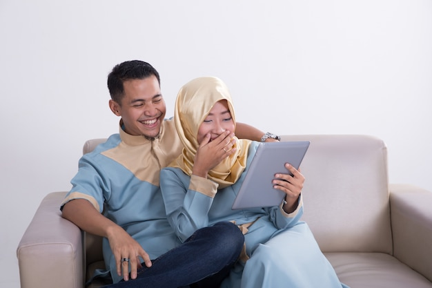 Muslim couple on a couch with tablet