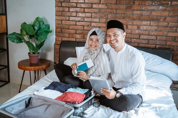 パスポートとタブレットを保持しているイスラム教徒のカップル