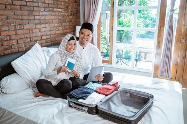 Мусульманская пара держит паспорт и планшет