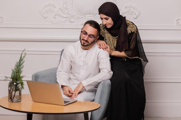 民族衣装を着たイスラム教徒のカップルは、ビデオ通信を介して通信します。友達とのビデオ会議。