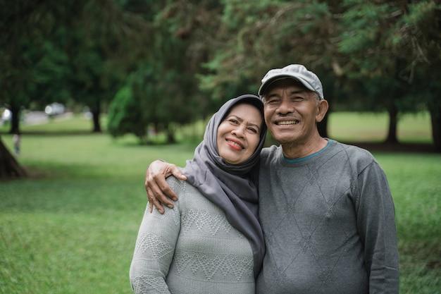 Мусульманская пара в парке улыбается и смотрит на камеру