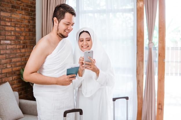 イスラム教徒のカップルがウムラとメッカ巡礼しながら電話をかける