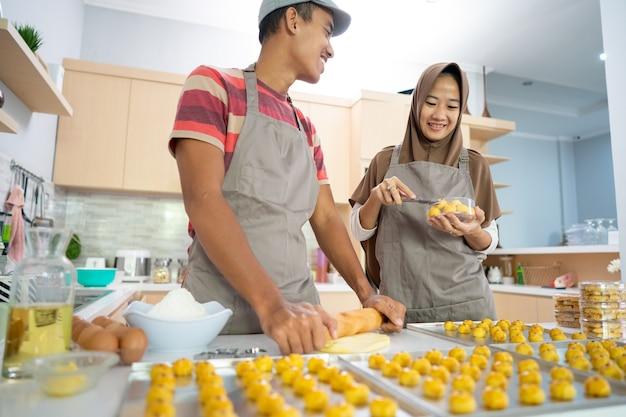 Мусульманская пара вместе готовит закусочный торт настар на кухне во время рамадана