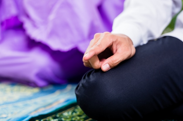 Muslim couple, man and woman, praying at home