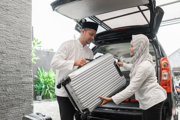 Muslim couple packing suitcase in the car