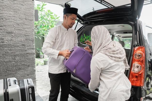 イスラム教徒のカップルが車の中でスーツケースを梱包