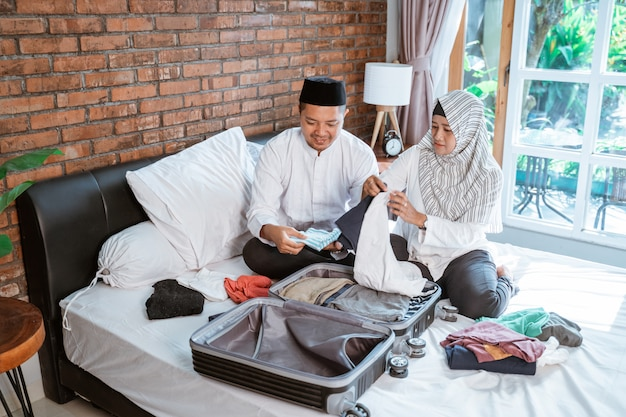Muslim couple preparing clothes on suitcase