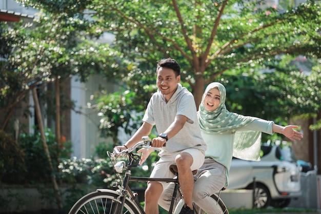 Muslim couple riding a bike