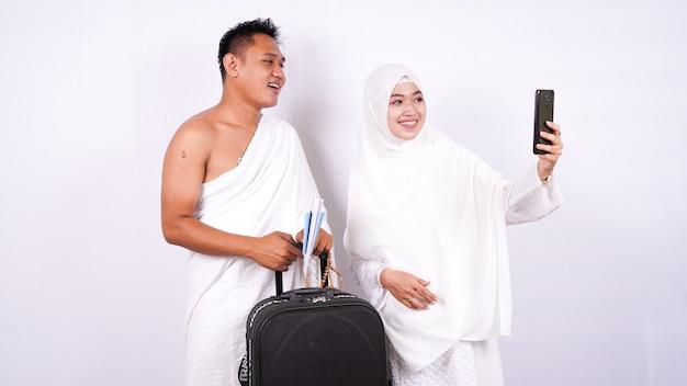 イスラム教徒のカップルは、分離された電話で自分撮りをします