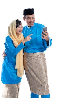 イスラム教徒のカップルが白い背景で隔離のスマートフォンを使用して家族と話す