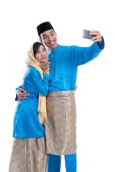 Мусульманская пара разговаривает с семьей с помощью смартфона, изолированного на белом фоне