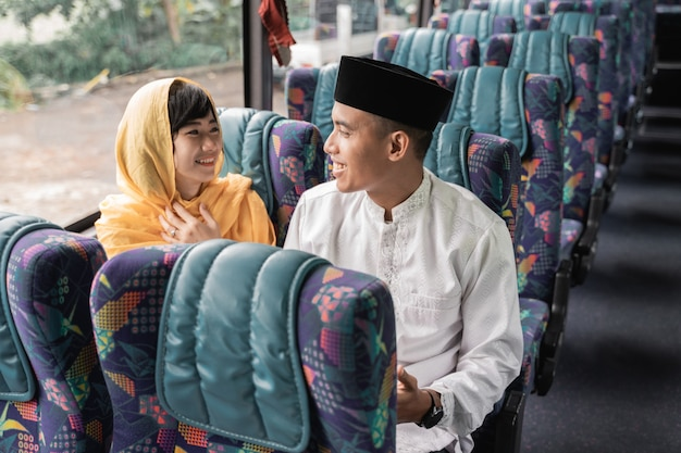 Muslim couple travel by bus during eid mubarak holiday to meet family at home