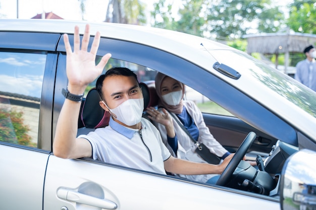 Muslim couple wearing masks waving from inside the car to the camera