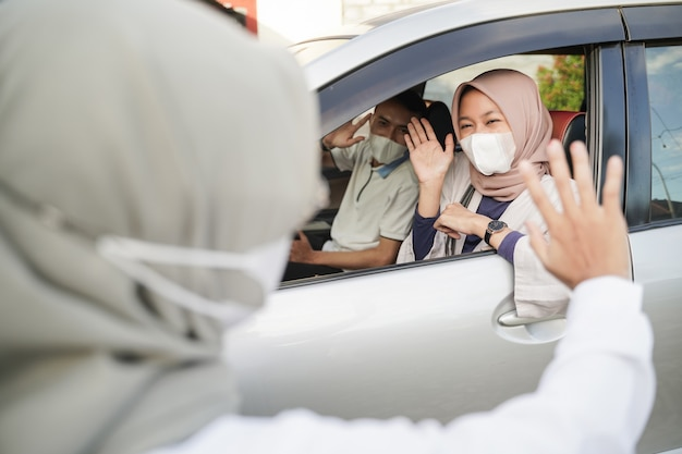 Muslim couple wearing masks waving from inside the car to a woman wearing a hijab