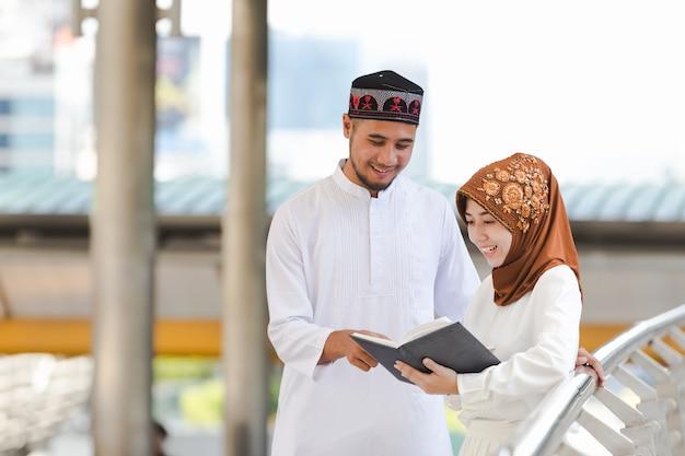 イスラム教徒のカップル若い女の子と男の子、都市で買い物をする読書、コンセプト教育とショッピング