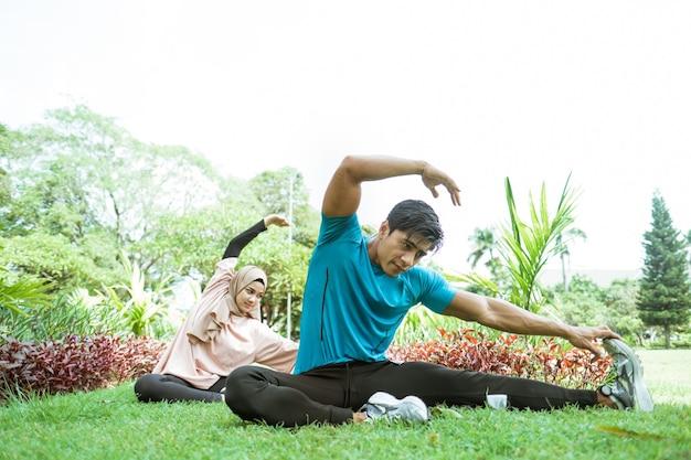 公園で屋外運動するときに一緒に脚の筋肉を訓練する動きをしているイスラム教徒のカップル