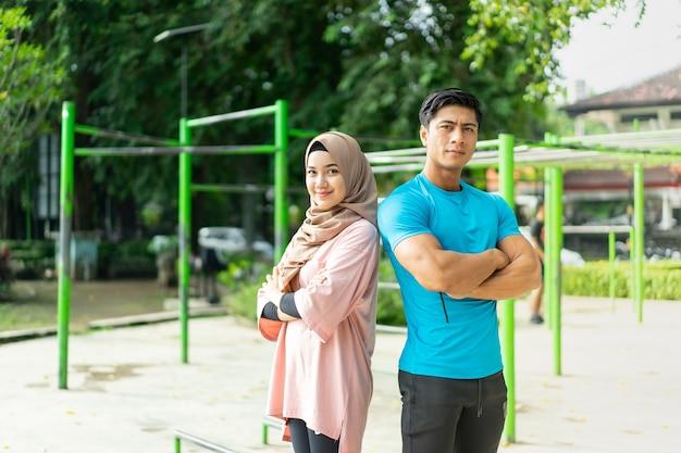 무슬림 커플은 공원에서 운동하는 동안 교차 손으로 등을 맞대고 서 있습니다.