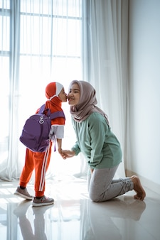 Muslim daughter shaking hand and kissing her mother before going to school