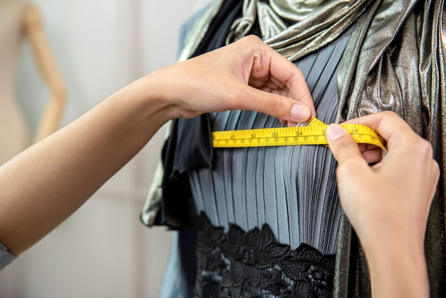 Muslim designer measuring size of dress with measurement tape