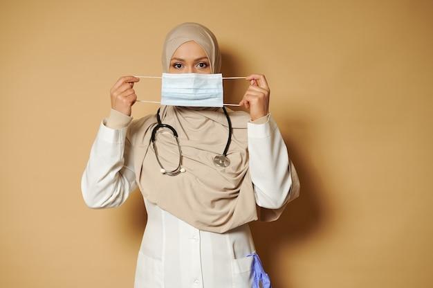Hijab 보유 및 베이지 색 표면 eith 복사 공간에 서있는 의료 마스크를 착용에 덮여 머리와 이슬람 의사