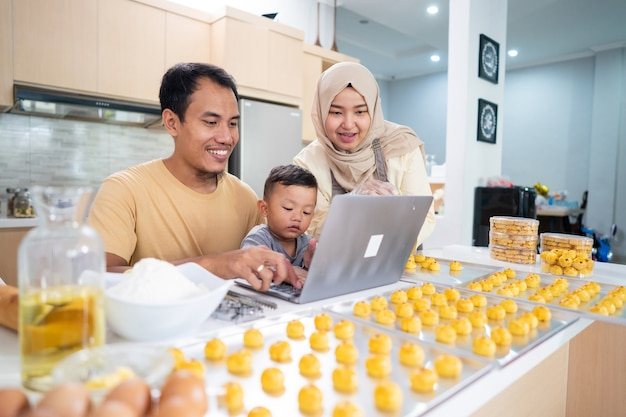 Muslim family cooking nastar tart at home together. father using laptop