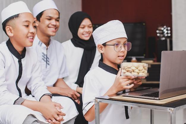 Eid 무바라크 축제 기간 동안 비디오 대화를하고 쿠키와 함께 노트북 앞에서 즐거운 시간을 보내는 이슬람 가족