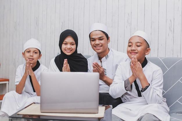 Мусульманская семья ведет видеобеседу перед ноутбуком с жестом приветствия руки для прощения на праздновании ид мубарак