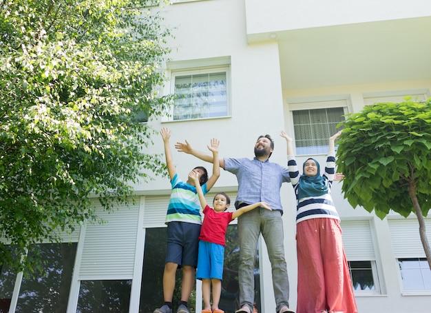 美しいモダンな家の前にイスラム教徒の家族