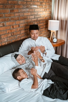 Muslim family pray on the bed