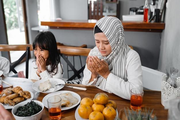 祈るイスラム教徒の家族。食事前に