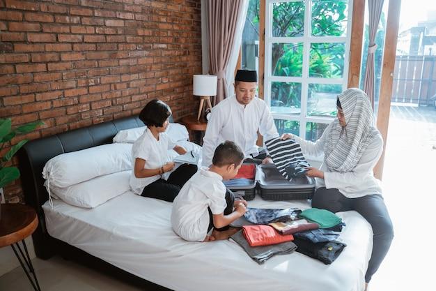 イスラム教徒の家族がmudikのときに携帯用の服を準備する