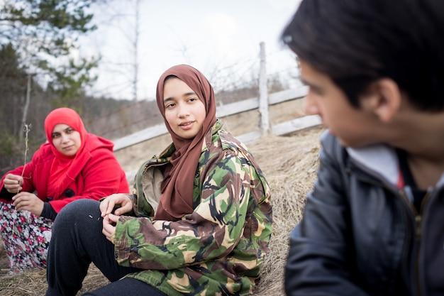 自然の田舎に座っているイスラム教徒の家族