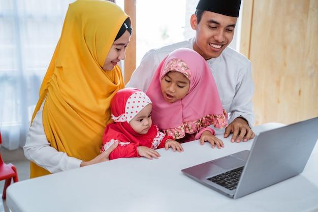 イスラム教徒の家族がラップトップを使用して友達に電話する