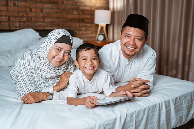 ベッドでタブレットを使用してイスラム教徒の家族