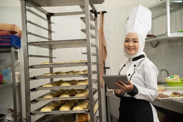 キッチンで働いてタブレットpcを保持しているイスラム教徒の女性ベイカー