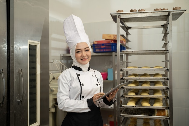 Muslim female baker working in the kitchen and holding tablet pc