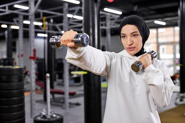 ダンベルで戦闘機のポーズで立っているヒジャーブの白いスポーツウェアのイスラム教徒の女性ボクサー、エクササイズをしている若いアラビアの女性、健康的なライフスタイルをリードしています。イスラム諸国のスポーツ、女性の権利の概念