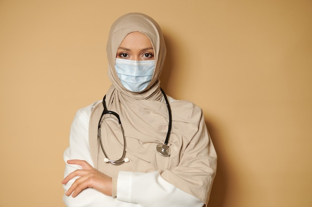 Hijab 및 의료용 블루 마스크 이슬람 여성 의사가 교차 팔을 앞에보고