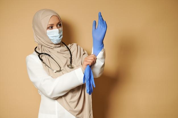 복사 공간 베이지 색 표면에 앞의 포즈 의료 보호 장갑을 끼고 덮여 머리와 이슬람 여성 의사