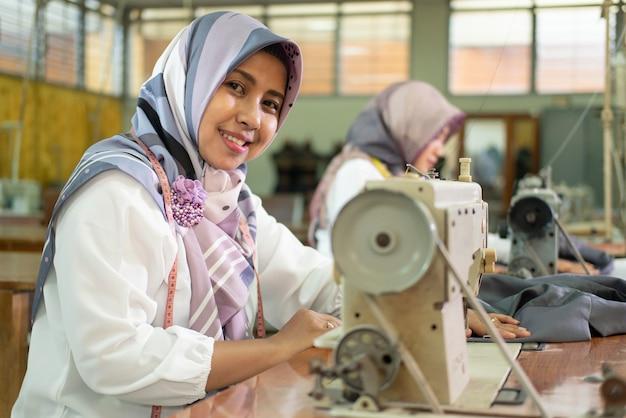 ミシンを使ってスカーフを身に着けているイスラム教徒の女性従業員が笑顔