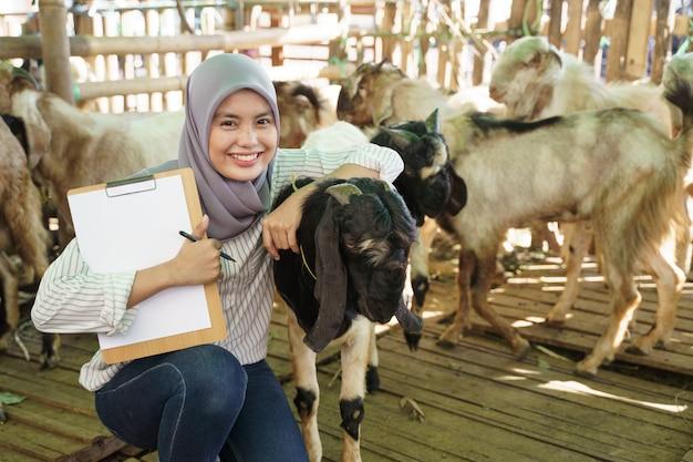 檻の中の彼女のヤギのチェックを行うイスラム教徒の女性農家