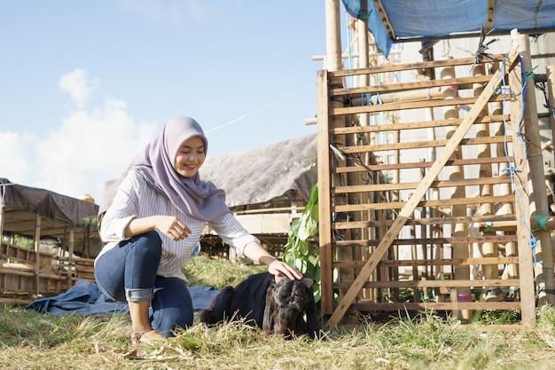 イスラム教徒の女性農家が伝統的な農場で動物に餌をやる