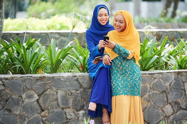 Muslim female friend with smartphone
