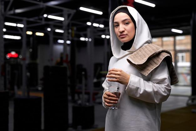 ジムでの激しいトレーニングの後、気分が良く、水を飲むイスラム教徒の女性。モダンなジムで、屋内で。